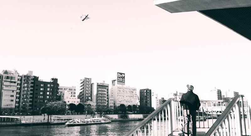 Hombre volando la cometa en el río